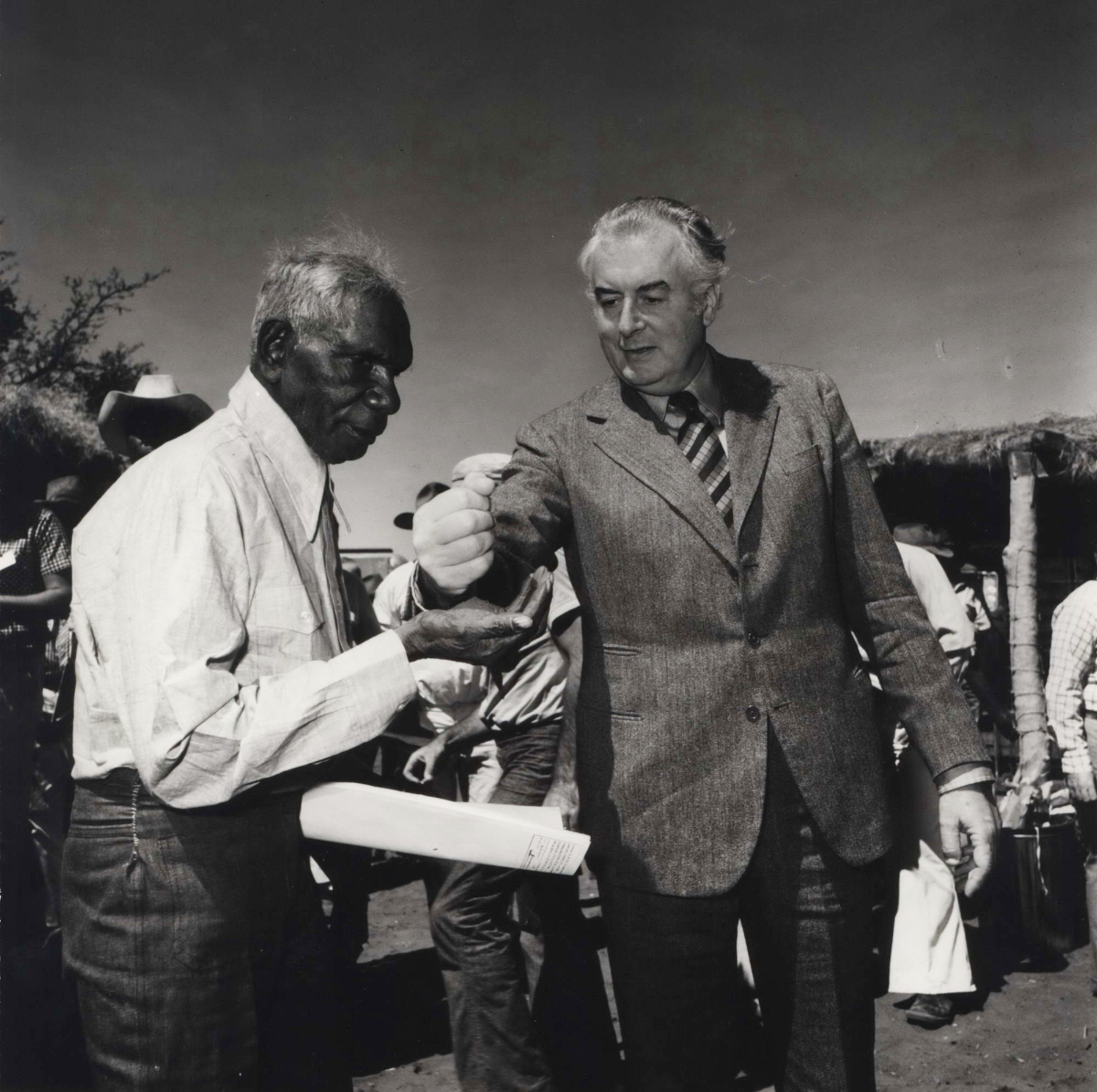 Gough Whitlam pouring soil into the hands of traditional owner Vincent Lingiari